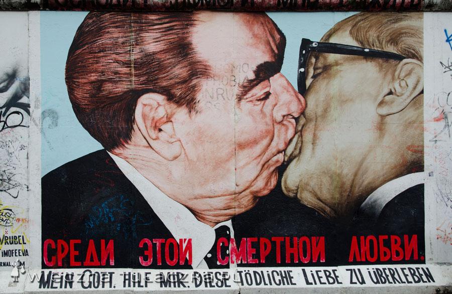 """Jedno z graffiti przedstawia najsłynniejszy i najbardziej namiętny pocałunek polityków, zwany """"braterskim"""". Bohaterami tej sceny są Breżniew i Honecker. Pocałunek został skonsumowany w 1979 roku, kiedy to obaj komunistyczni przywódcy spotkali się z okazji 30-lecia powstania Niemieckiej Republiki Demokratycznej. Ponoć do dziś trwają spory, który z wodzów wpijał się w usta drugiego, a który tylko odwzajemniał pocałunek ;)"""
