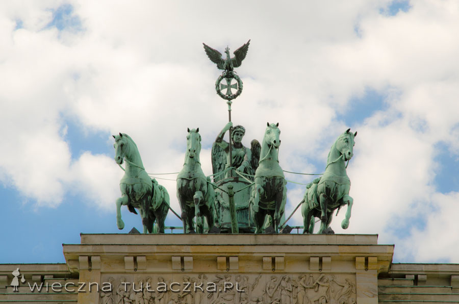 Bramę wieńczy rzeźba 4-konnej kwadrygi, prowadzonej przez rzymską boginię zwycięstwa - Wiktorię. Sam Napoleon zabrał figurę do Paryża, ale po obaleniu cesarza wróciła ona do Berlina. W 1814 roku rzeźbę odpicowano, dodając Żelazny Krzyż, nowy symbol władzy zaprojektowany przez Schinkela.