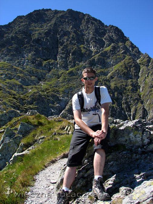 Mięguszowiecki Szczyt Czarny, to w tle, bo na froncie siedzi Tomek ;) Mniej więcej na wysokości jego głowy przebiega trawers na Przełęcz pod Chłopkiem.